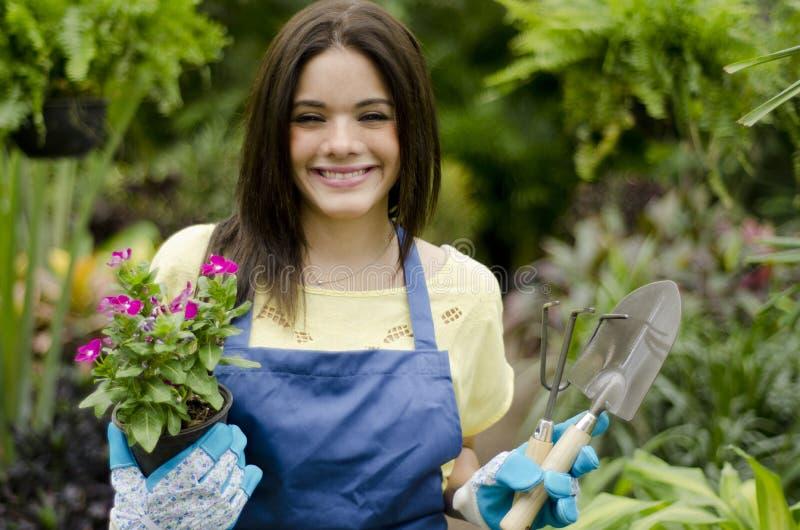爱她的工作的逗人喜爱的花匠 库存图片