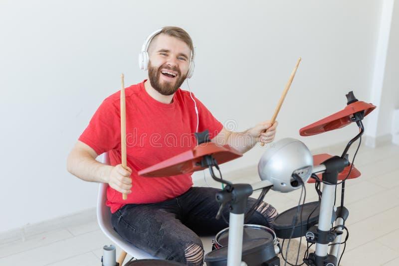 爱好、音乐和人概念-在轻的背景的鼓手人 库存照片