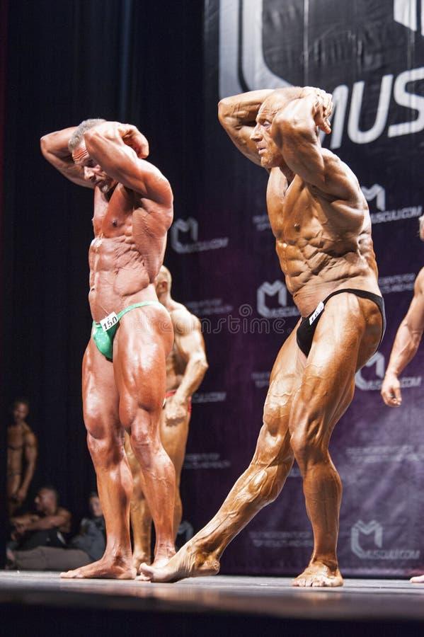 爱好健美者在冠军显示他们的abdominals和大腿在阶段 图库摄影