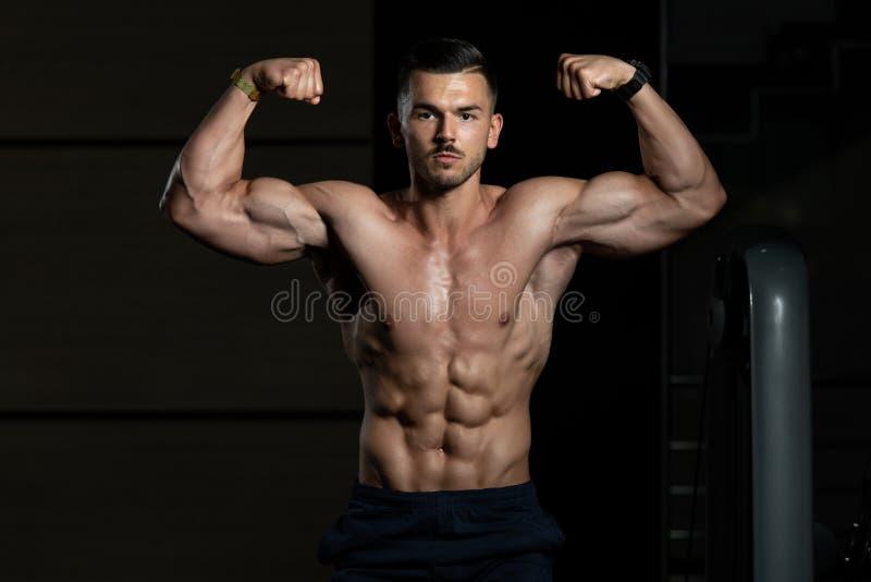 爱好健美者执行的前面双重二头肌在健身房摆在 库存图片