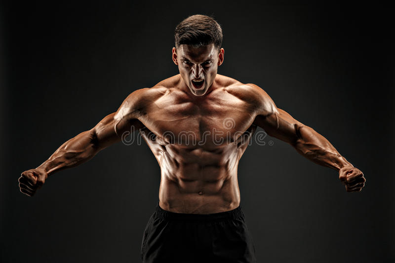 爱好健美者摆在 黑暗的背景的健身肌肉的人 咆哮刺激的 免版税库存照片