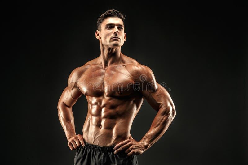 爱好健美者摆在 黑暗的背景的健身肌肉的人 免版税图库摄影
