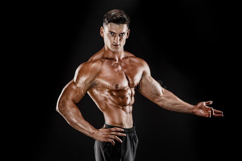 爱好健美者摆在 黑暗的背景的健身肌肉的人 库存照片