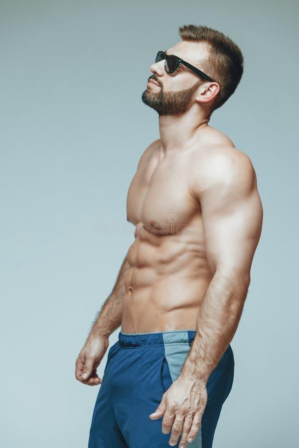 爱好健美者摆在 美好的运动的人男性力量 在蓝色短裤和太阳镜干涉的健身 在被隔绝的灰色 免版税库存图片