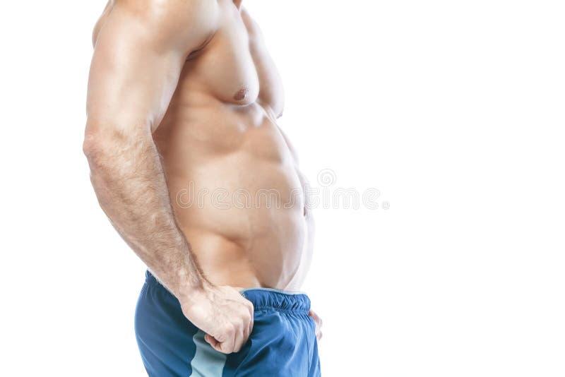 爱好健美者摆在 美好的运动的人男性力量 在蓝色短裤干涉的健身 在被隔绝的白色背景 人 库存图片