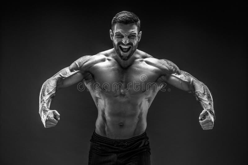 爱好健美者摆在 黑暗的背景的健身肌肉的人 吼声 免版税库存图片