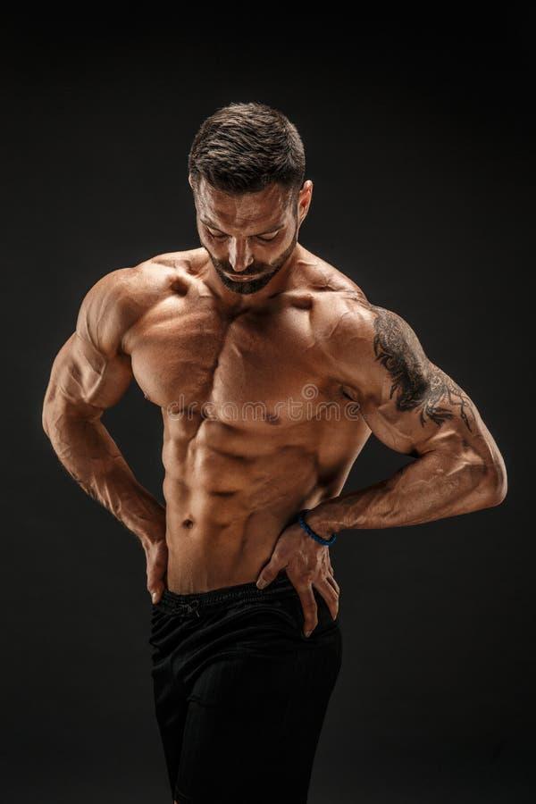 爱好健美者摆在 黑暗的背景的健身肌肉的人 免版税库存图片