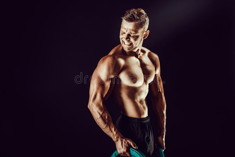爱好健美者摆在 黑暗的背景的健身肌肉的人 免版税库存照片