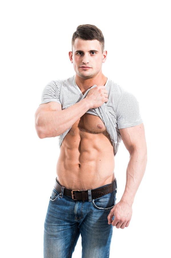 爱好健美者陈列新闻 一个人显示他的腹肌,被上升的手T恤杉 按,建身 炫耀人 免版税图库摄影