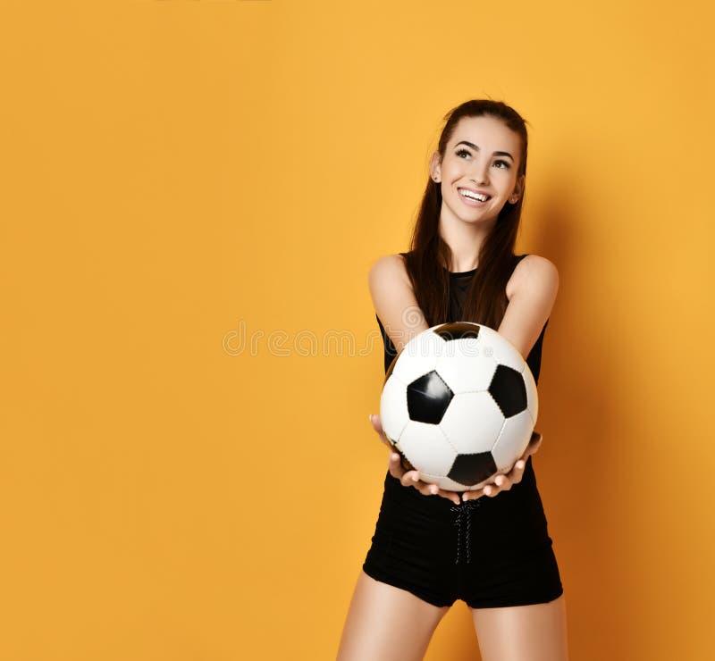 爱好者体育黑制服的妇女球员递了我们足球和微笑在背景与大方的本体拷贝空间 免版税库存图片