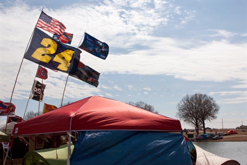 爱好者挂NASCAR旗子,当野营在赛马跑道之外时 库存图片