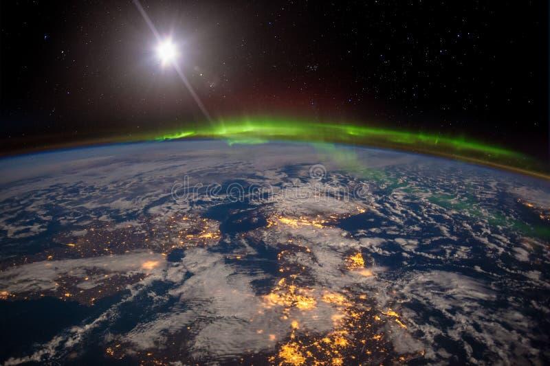 爱尔兰、英国和斯堪的那维亚在被月光照亮夜在惊人的极光下 免版税库存图片