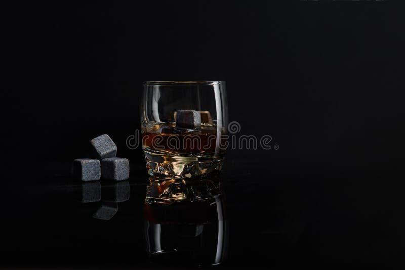爱尔兰威士忌酒 杯与wiskey石头的威士忌酒 在黑背景的Wiskey石头 典雅的杯威士忌酒 免版税库存照片
