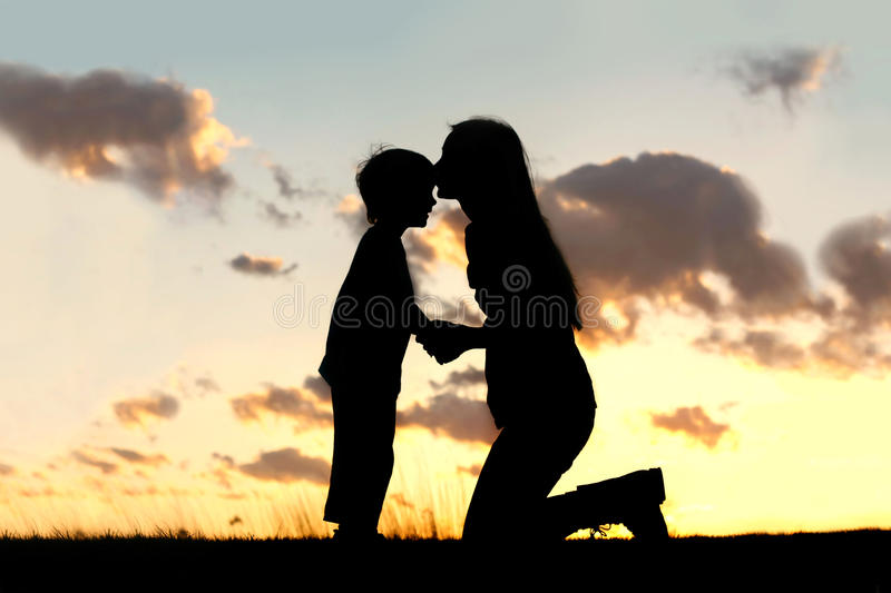 爱恋亲吻小孩的母亲在日落 免版税库存照片