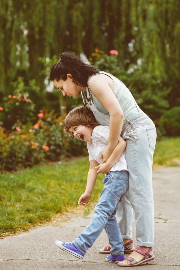 爱恋的使用在夏天的母亲和笑的儿子 免版税库存图片