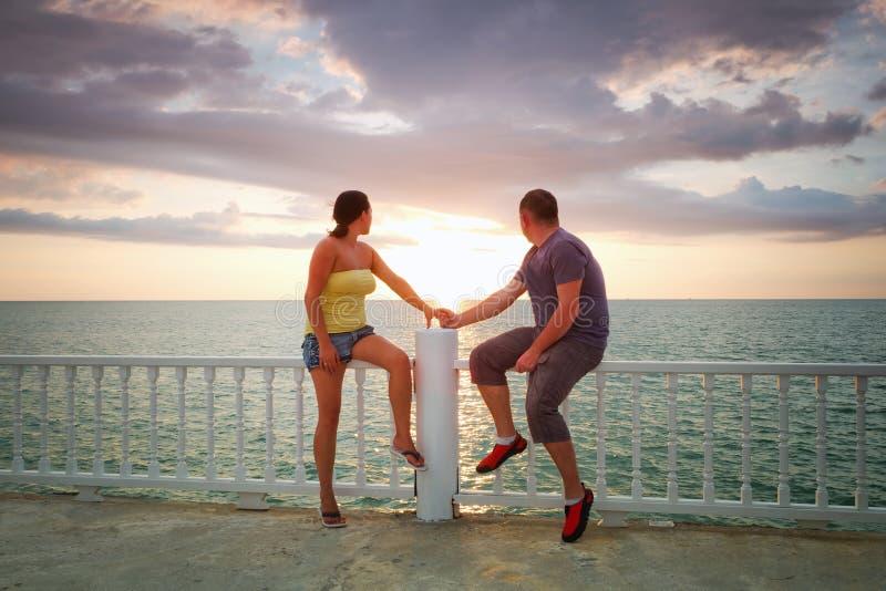 爱恋的在海运的夫妇注意的日落 免版税库存照片