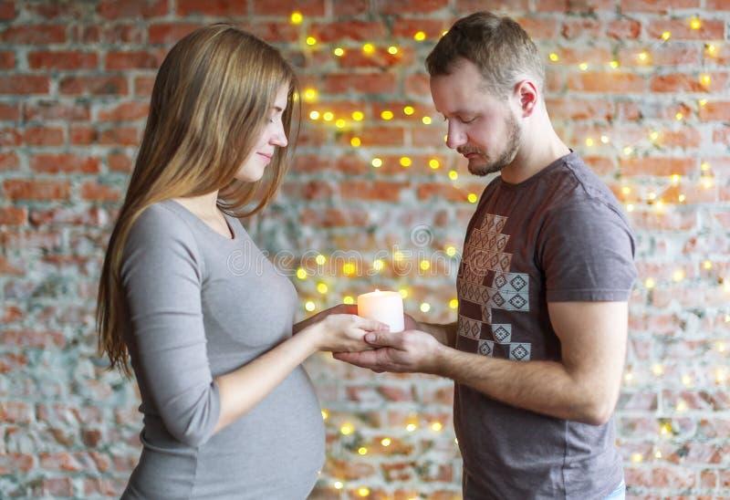 爱恋的夫妇举灼烧的蜡烛手中 妇女怀孕 库存图片