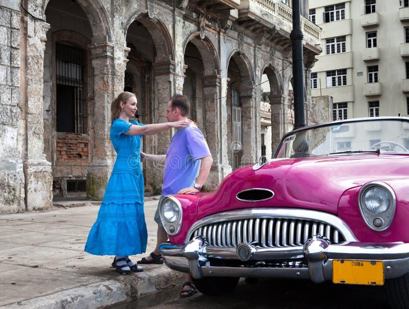 爱恋的夫妇在哈瓦那旧城临近老美国减速火箭的汽车(上个世纪的第50岁月)在Malecon街道2013年1月27日上, 免版税库存图片
