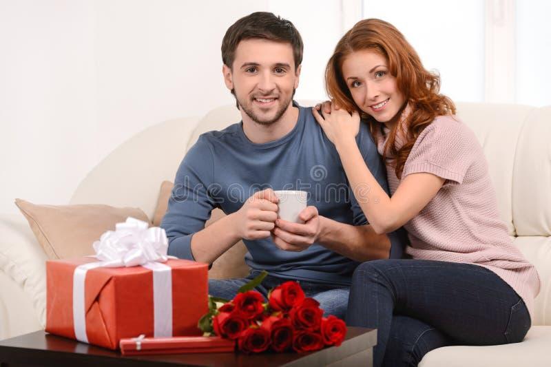 爱恋的夫妇在家。坐有吸引力的年轻爱恋的夫妇  库存图片