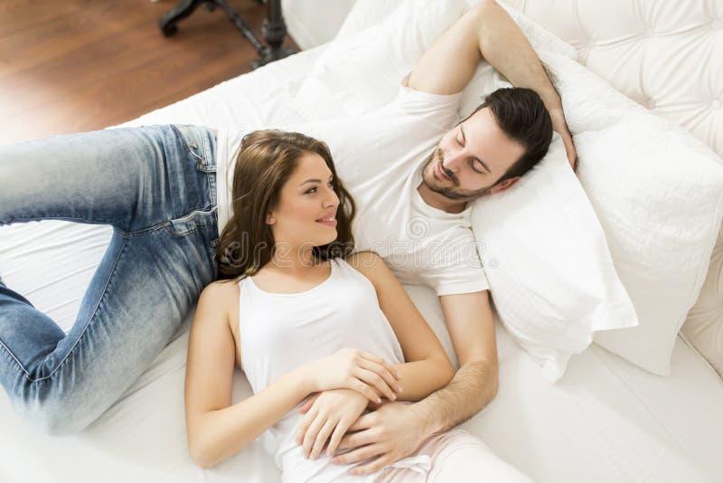 爱恋的夫妇在床上 免版税库存图片