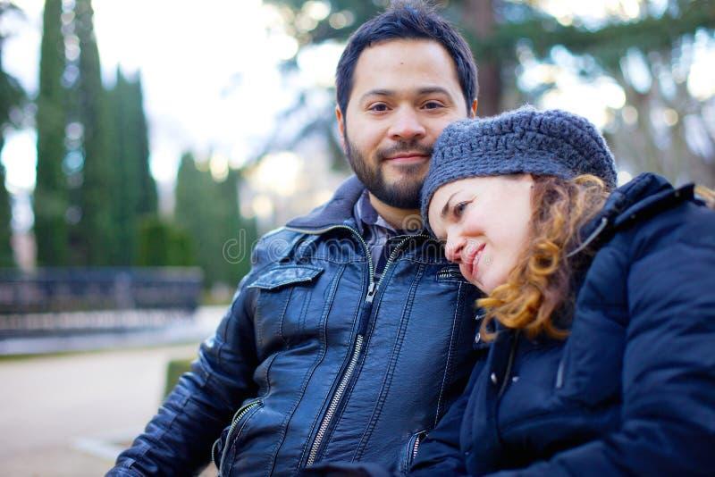 爱恋的夫妇坐公园长椅 免版税库存照片