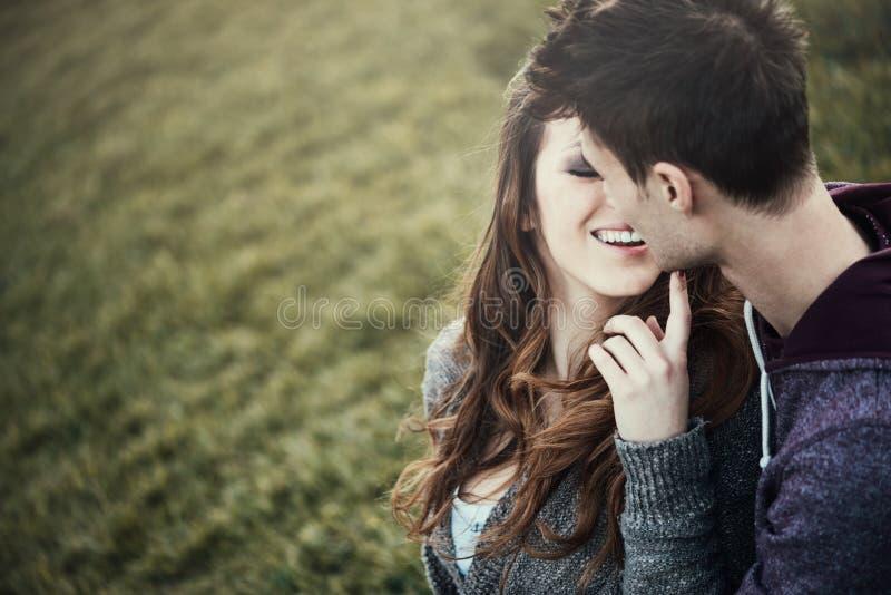 年轻爱恋的夫妇坐草 图库摄影