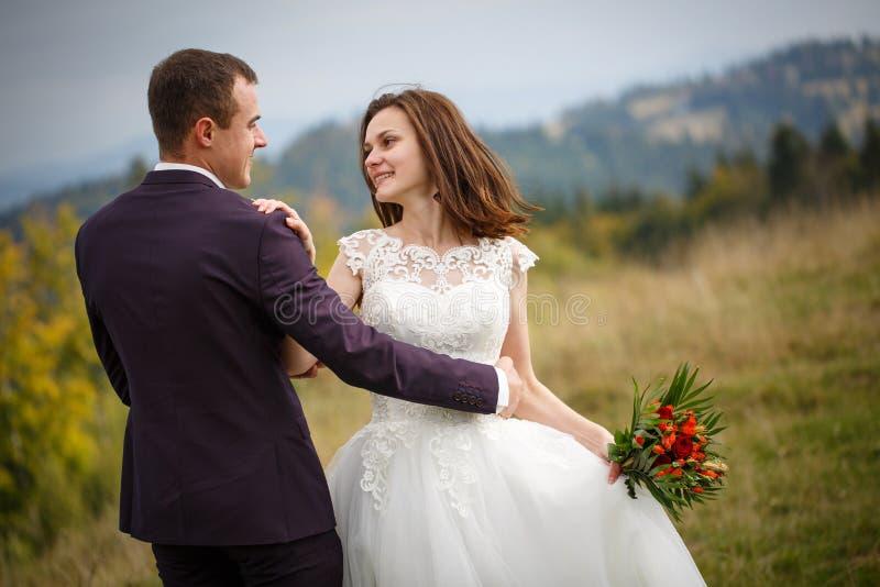 爱恋的夫妇是山的新婚佳偶 有花束的时髦的新娘亲吻新郎 爱,保真度和 库存照片