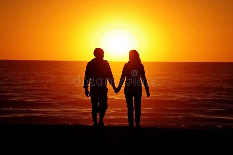 爱恋的夫妇海滩日落 库存照片