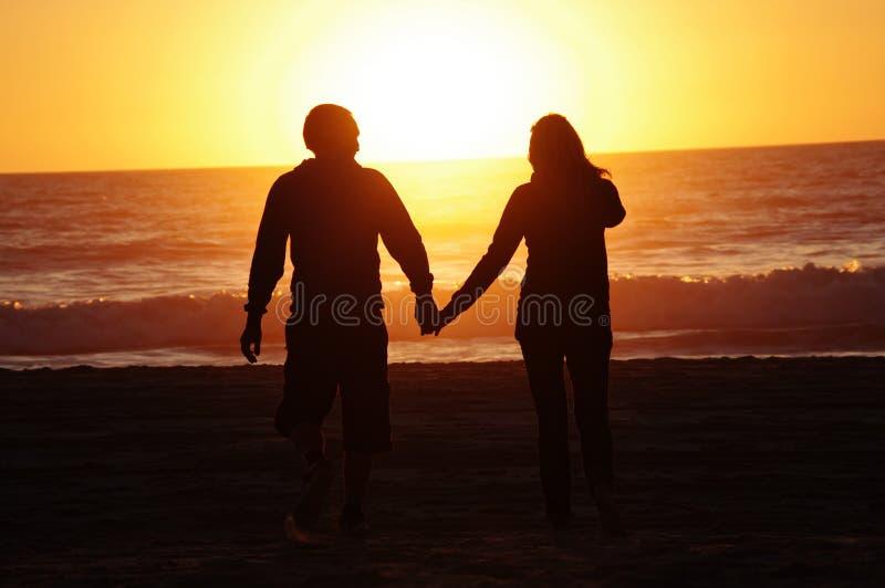 爱恋的夫妇海滩日落 库存图片