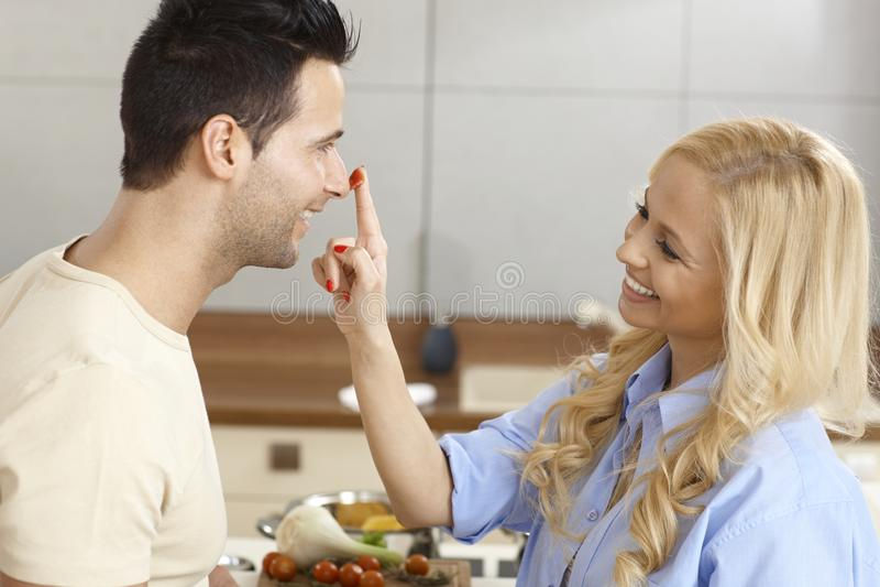 爱恋的夫妇获得乐趣在厨房 库存照片