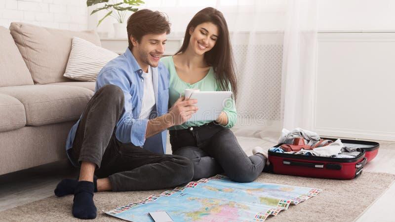 爱恋的夫妇计划的假期旅行和使用片剂 库存图片