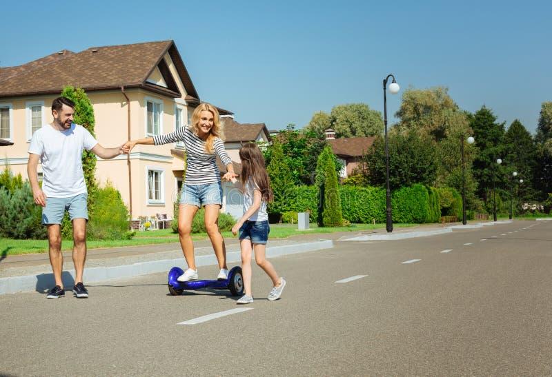 爱恋的家庭支持的妇女骑马hoverboard 库存图片