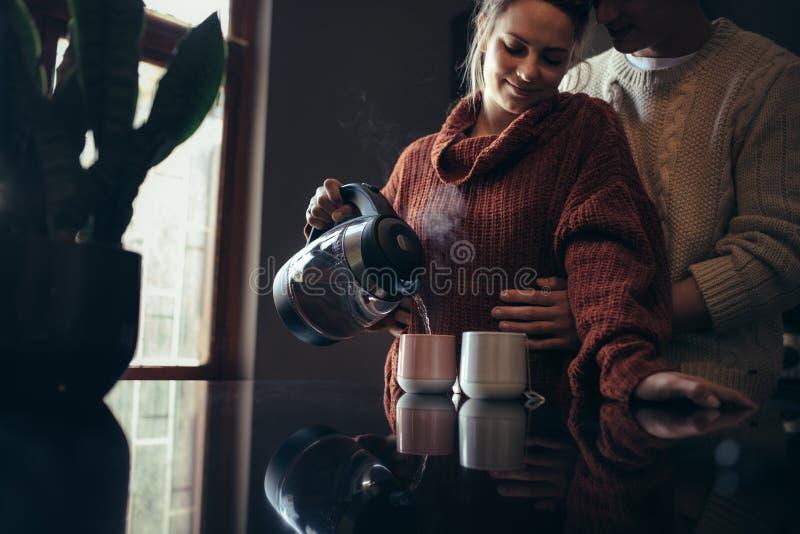爱恋的年轻夫妇在做咖啡的厨房里 免版税库存照片