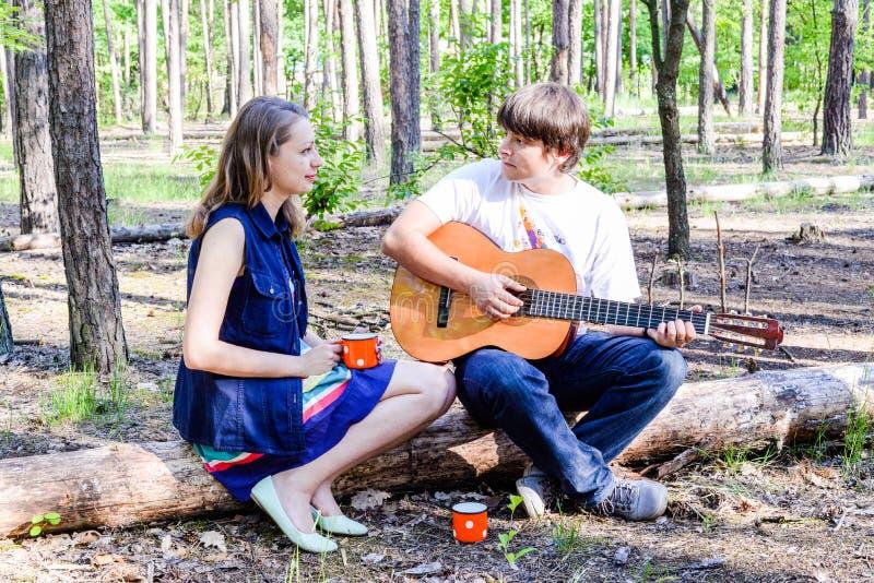 年轻爱恋的愉快的加上画象吉他在森林里 免版税库存图片