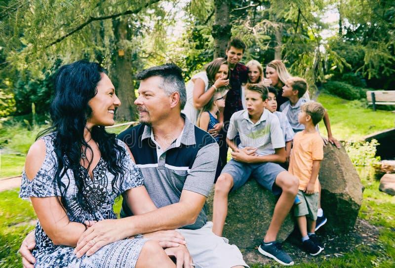 爱恋的成熟夫妇和九个孩子在公园 库存照片
