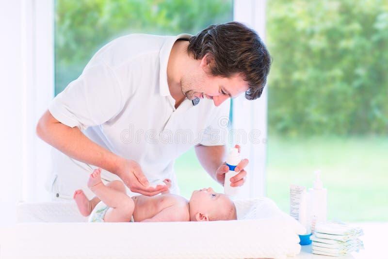 年轻爱恋的新出生的儿子父亲改变的尿布  免版税图库摄影