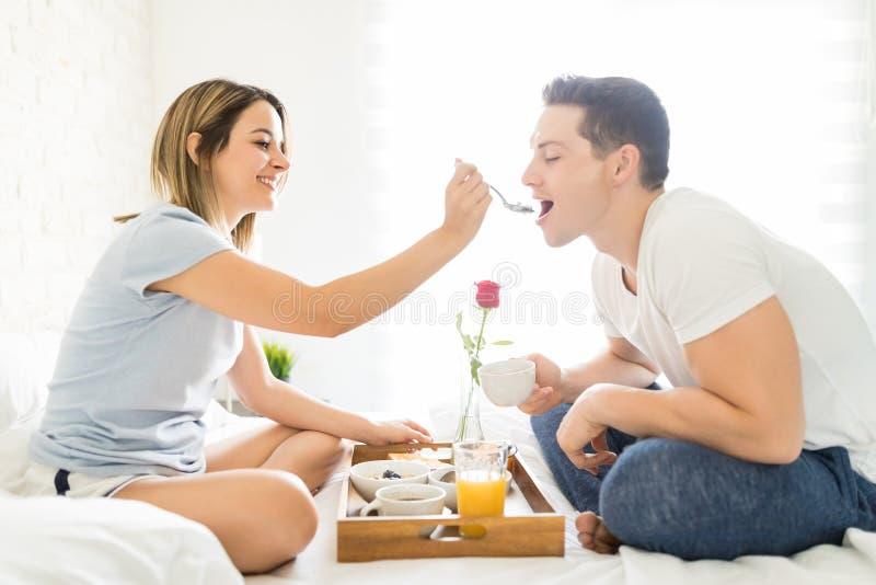爱恋的有早餐的女朋友哺养的人在床上 库存照片