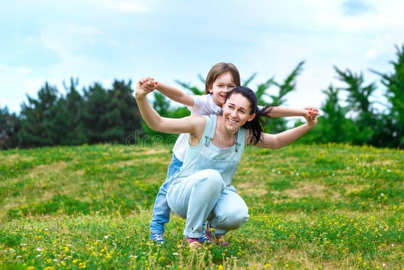 爱恋的母亲在小儿子后面滚动在公园 库存图片