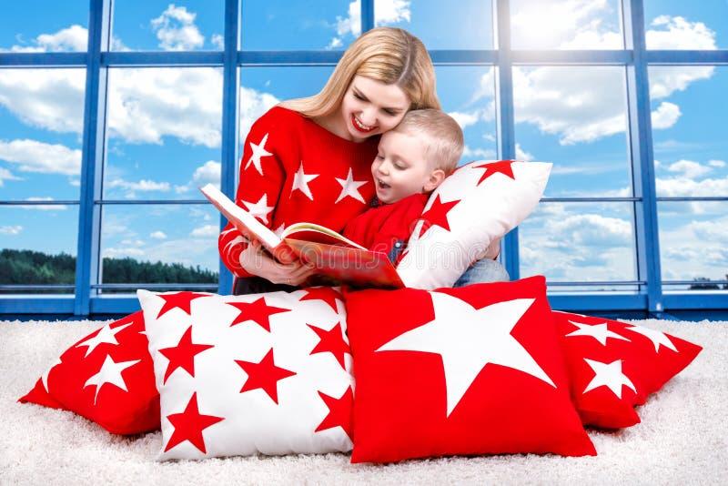 爱恋的美丽的年轻母亲读一本书给他的小儿子 说谎在室内装璜的枕头在Th背景中  库存图片