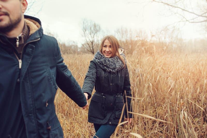 爱恋的年轻夫妇愉快室外在舒适在秋天森林里一起温暖步行 免版税库存照片
