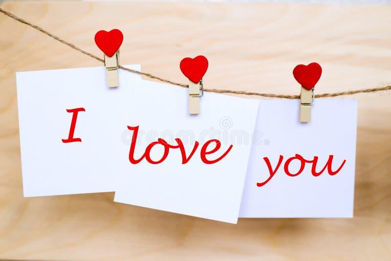 爱您在垂悬在心脏形状别针的贴纸的文本 免版税库存照片
