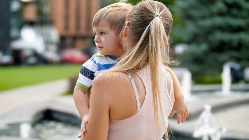 爱抚和镇定她哭泣的小孩儿子的年轻母亲画象在公园 图库摄影