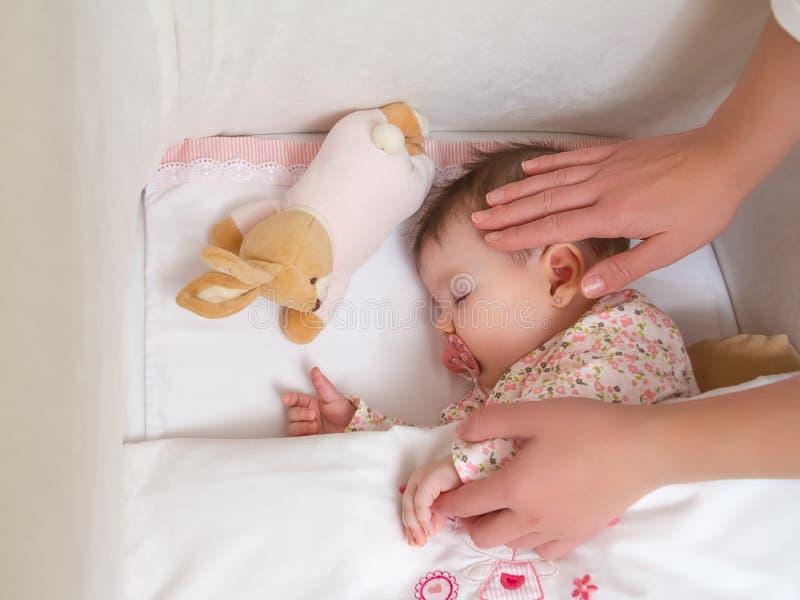 爱抚她女婴睡觉的母亲的手 免版税库存照片