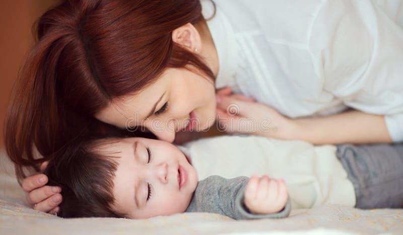 爱抚她新出生的婴孩的少妇 免版税库存图片