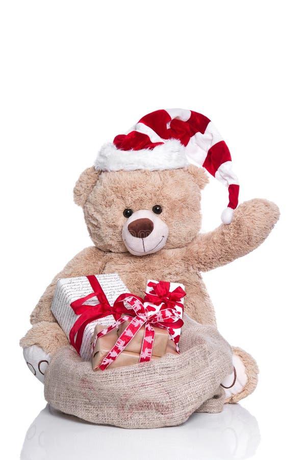 爱拥抱玩具熊挥动的,佩带的圣诞节帽子和礼物盒  免版税库存图片