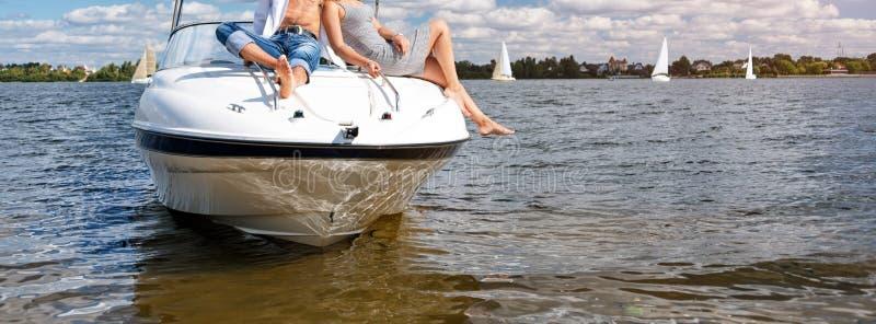 爱放松在游艇的夫妇或朋友,享用太阳在晴朗的夏日 垂悬从小船的腿漂浮在 库存图片