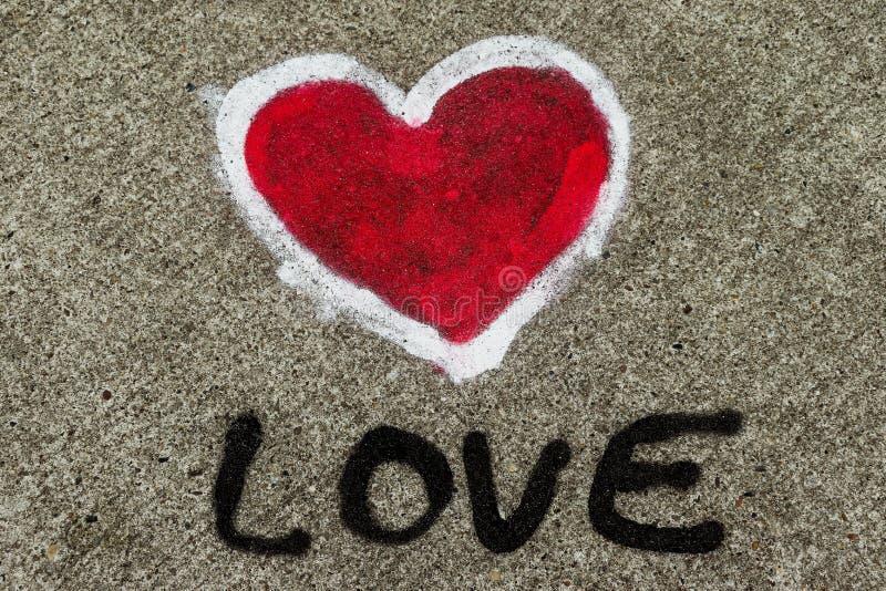 爱文本和红心形状与被绘的白色概述在巨型的混凝土墙上喷洒了 创造性的概念象征性为爱 免版税库存图片