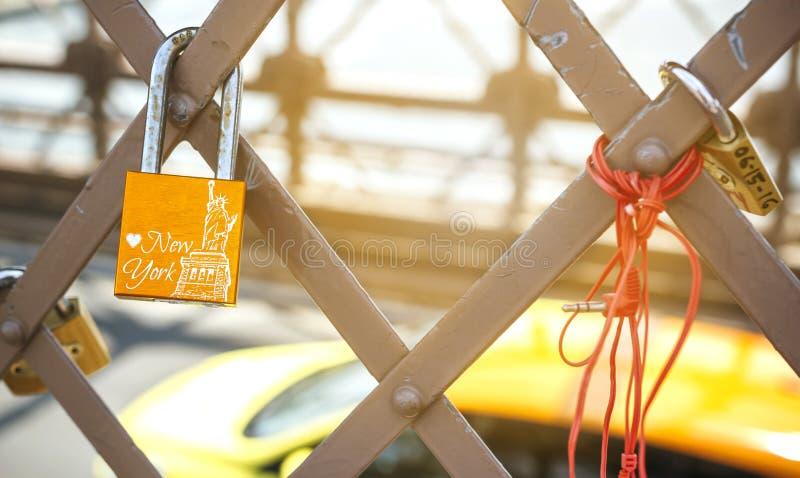 爱有自由女神像的锁和在背景的黄色小室 库存图片