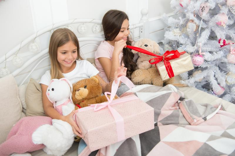 爱每件礼物他们接受 新的惊奇年 愉快的小孩子拿着礼物盒 有礼物的小女孩在床上 免版税库存图片