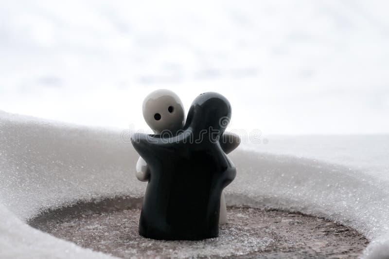 爱熔化冰华伦泰` s天概念 F女孩和男孩玩偶互相拥抱,站立在与被弄脏的backg的白色雪 库存照片